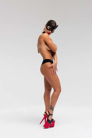 Sexy topless woman in black mask
