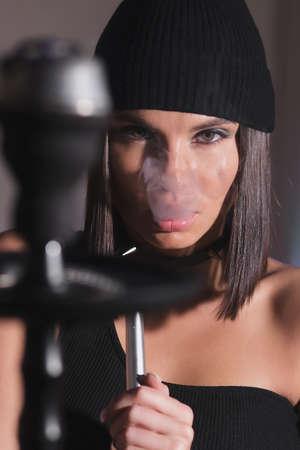 Brunette smoking hookah in dark room