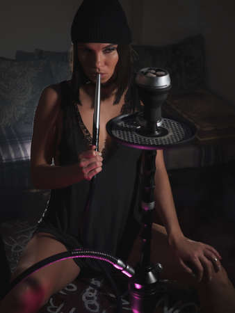 Sensual woman smoking hookah in darkness