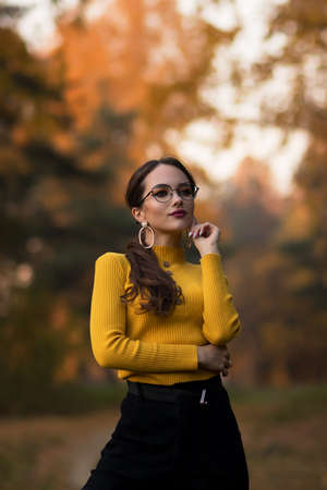Charming young woman standing in autumnal park