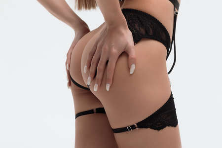 Faceless female with hands on legs posing in studio
