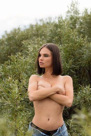 Topless woman standing amidst bushes Banco de Imagens