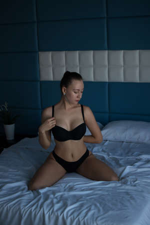 Sensual woman in lingerie sitting on bed Banco de Imagens