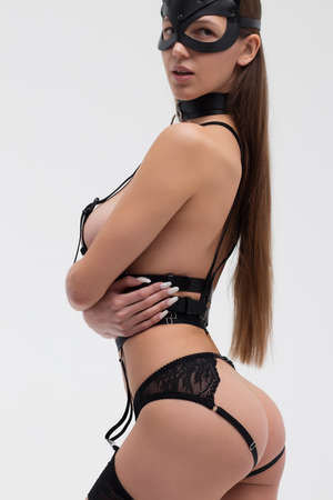 Sensual woman in mask embracing body Banco de Imagens