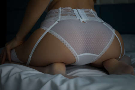 Anonymous woman in erotic white lingerie in bed