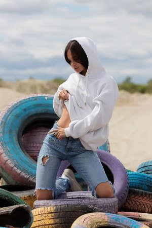 Stylish woman touching belly on beach