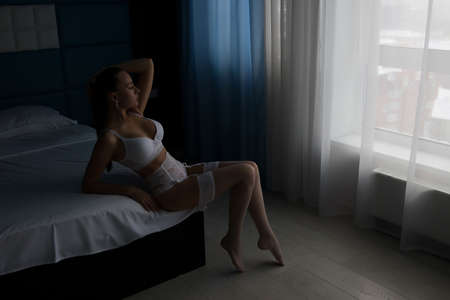 Seductive woman in lingerie sitting on bed