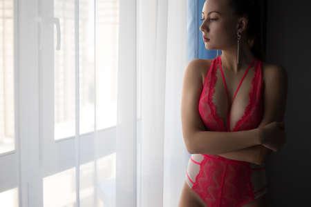 Alluring woman in red underwear standing near window