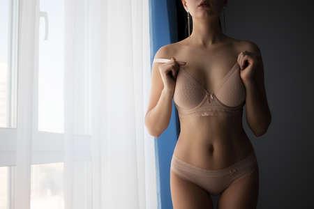 Alluring woman in underwear standing near window
