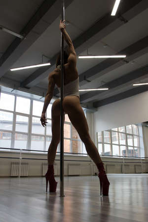 Unrecognizable sexy woman performing alluring pole dance