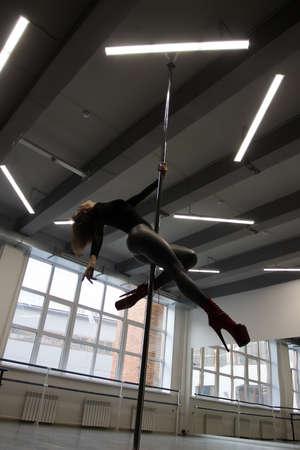 Slim woman dancing on pole