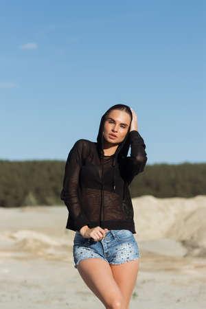 Alluring brunette in mesh hoodie on beach