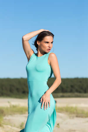 Gorgeous woman in flying dress on sand