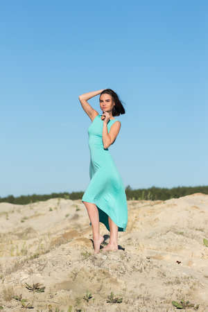 Gorgeous woman in flying dress on sand Standard-Bild