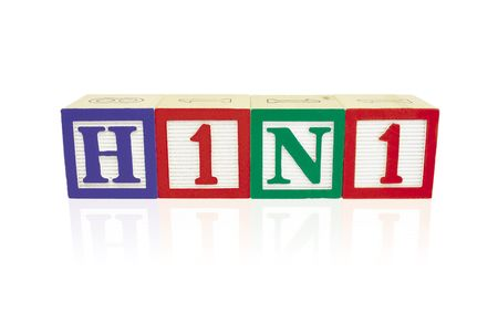 Alphabet blocks arranged horizontally on a reflective white surface to spell 'H1N1' Stock Photo - 6053532