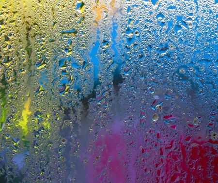 Condensation on window glass with blurred colors, primarily yellow, blue and red, in the background.
