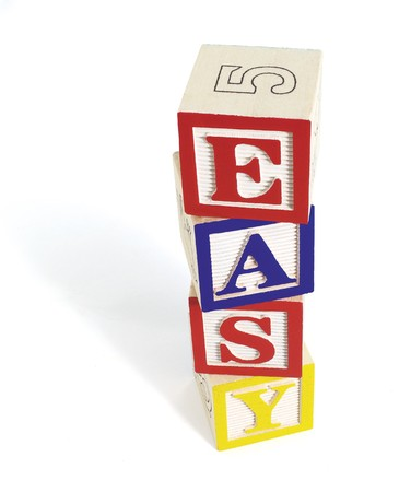 Four wooden alphabet blocks on white background, stacked to form the word, easy. Stack of blocks casts a shadow. Stock Photo