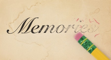 Close up of a yellow pencil erasing the word, memories from old, yellowed paper