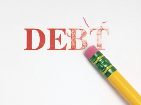 Close up of a yellow pencil erasing the word, debt in red. Stock Photo