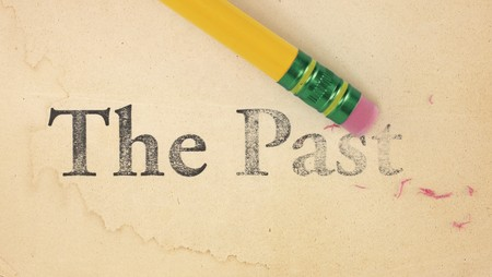 Close up of a yellow pencil erasing the words, 'The Past' from old, yellowed paper Stockfoto
