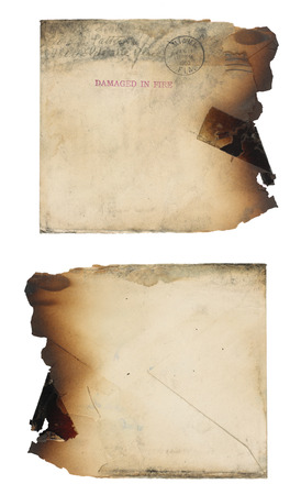 soot: The the front and back of a grungy, yellowing, fire-damaged envelope.  Envelope is soot stained and the right edge is completely burned away. Isolated on white. Stock Photo