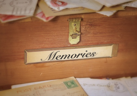 A simple, old wooden box with a brass latch and label holder containing the word, memories. Old letters and postcards are piled up in front and on top of the box.  A very narrow DOF reminds the viewer of the increasing fuzziness of memories far in the p