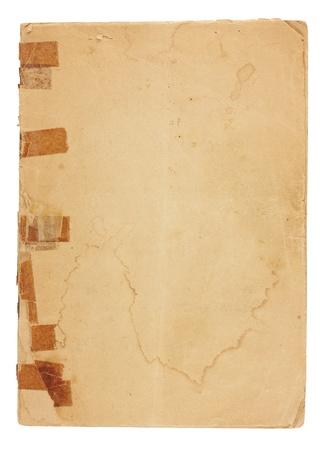 Een oude pamflet met zeer oude, vergeelde tape op de verbroken binding van boven gezien.  Het voorblad is water gekleurd, gescheurd en vergeling met ruwe randen en ezelsoren hoeken en is leeg met ruimte voor tekst en afbeeldingen. Geïsoleerd op wit