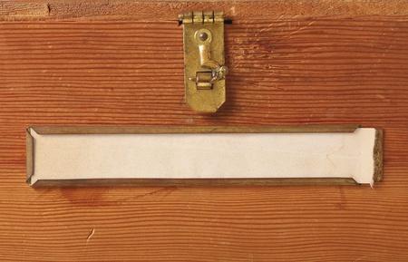 真鍮ラッチとラベル ホルダーを空白で準備ができてあなたのテキストのラベルを黄変の特徴シンプルな木製の箱の前面のクローズ アップ。
