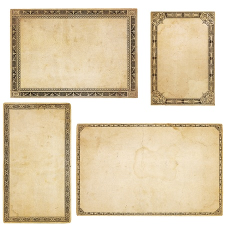 white textured paper: A set of four heavily aged blank cards with stains, creases and tears, old-fashioned decorative border. Isolated on white. Stock Photo
