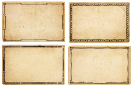 creases: A set of four heavily aged, blank cards with stains, creases and tears.  Each card has different, old-fashioned decorative border. Isolated on white. Includes clipping paths.