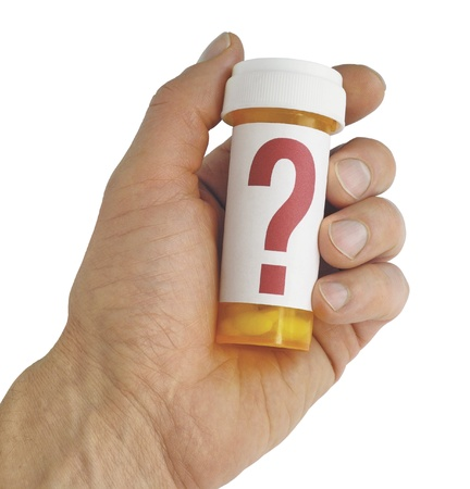 Close up of a hand holding a yellow pill bottle with a large red question mark on the label. Isolated on white. Includes clipping path.