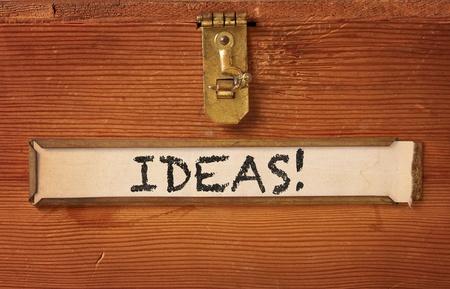 真鍮ラッチとラベル ホルダーを備えたシンプルな木製の箱の前面。「アイデア」は、黄変のラベルに書かれた手です。 写真素材 - 13159957