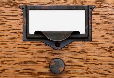 Close up of a blank, white label in a grungy, tarnished brass label holder and drawer pull on an oak filing cabinet drawer.