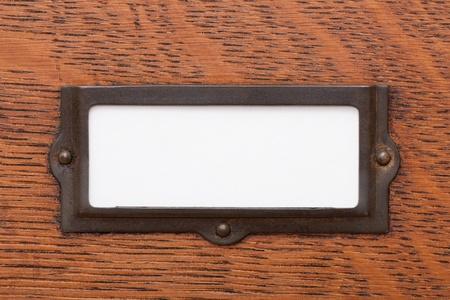 Close-up van een leeg, wit etiket in een oude messing etikethouder op een eiken archiefkast lade.