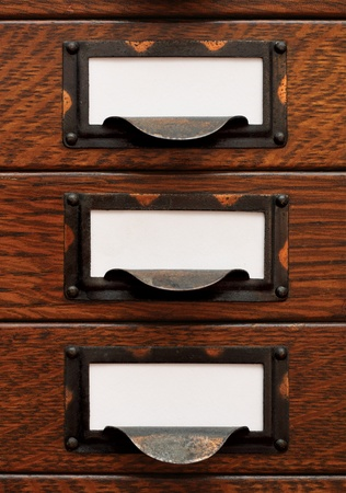 Vertical stack of three small, old oak flat file drawers with white empty tags in tarnished brass label holders