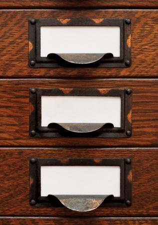 Verticale stapel van drie kleine, oude eiken flat file laden met witte lege tags in bezoedelde messing etikethouders