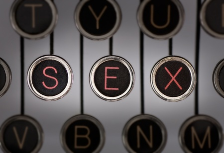 Close up of old typewriter keyboard with scratched chrome keys with black centers and white letters. Lighting and focus are centered on for keys spelling out SEX.  Stock Photo