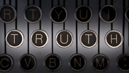 Image of old typewriter keyboard with scratched chrome keys that spell out the word TRUTH. Lighting and focus are centered on TRUTH. Stock Photo