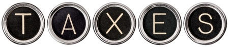 Old, scratched chrome typewriter keys with black centers and white letters spelling out TAXES