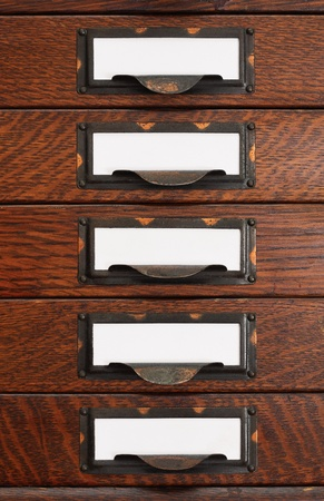 label: Vertical stack of five old oak flat file drawers with white empty tags in tarnished brass label holders.