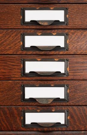 Verticale stapel van vijf oude eiken flat file laden met witte lege tags in bezoedelde messing etikethouders. Stockfoto
