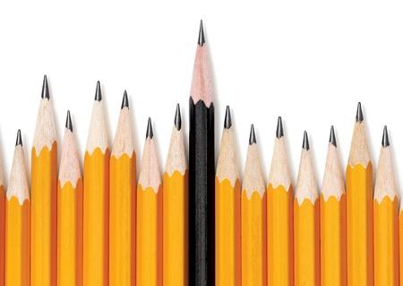 Ongelijke rij van gele potloden met een zwart potlood in het midden stijgende groter en opstaan uit dan de rest. Op wit met druppel schaduw