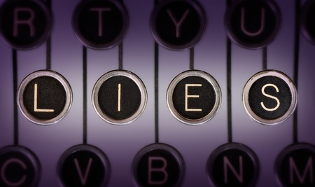 Close up of old typewriter keyboard with scratched chrome keys that spell out LIES. Lighting and focus are centered on LIES.  photo