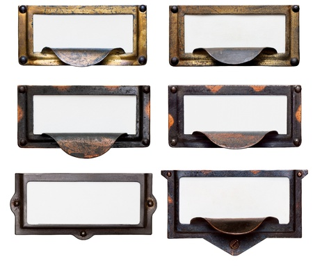 label: Collection of six old, tarnished brass file drawer label holders and drawer pulls with blank cards. Isolated on white.  Stock Photo