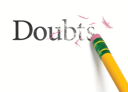 skepticism: Close up of a yellow pencil erasing the word, Doubts. Isolated on white.