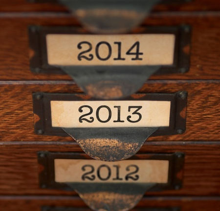 tarnished: Stack of old, oak flat file drawers with years 2012, 2013, and 2014 printed on tags in tarnished brass label holders. Shallow DOF with focus on 2013.