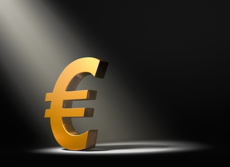 A gold Euro symbol on a black background and illuminated by a single, yellow spotlight  Banco de Imagens