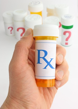 medicine bottle: A hand holding a medicine bottle marked with an Rx pharmacy mark. A variety of pill bottles labeled with large question marks are in the background.
