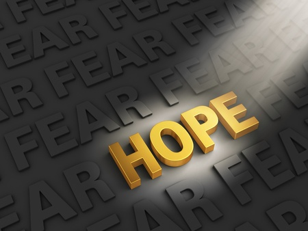 A spotlight illuminates a bright, gold  HOPE  on a dark background with rows of  FEAR  Stock Photo