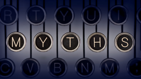 Close up of old manual typewriter keyboard with scratched chrome keys that spell out  MYTHS    Lighting and focus are centered on  MYTHS    Imagens